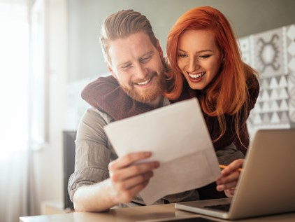bearded man and red headed woman with paperwork