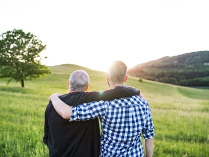 adult man with arm around his father looking into hillside