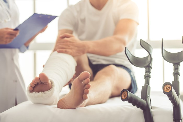man sitting on hospital bed with broken leg