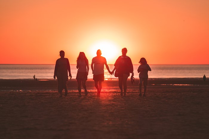 family walking into sunset on a beach