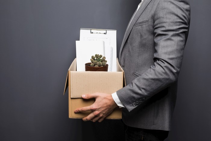 Fired employee hiding behind box with personal items